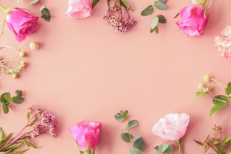 広げられたリングノートとピンクのボールペン。ノートパソコン。ミルクティーの入ったカップ&ソーサ。ピンクのはさみ。