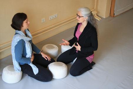 Eine Frau erklärt einer anderen Frau etwas über Energiearbeit, beide sitzen auf Yogakissen auf dem Boden in einem Yogastudio oder einem Coachingstudio