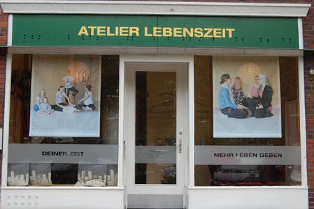 Schaufenster des Studios Atelier Lebenszeit, das Ladenschild ist grün mit gelber Schrift, es hat zwei gleichgroße Schaufenster, in denen großformatige Bilder auf Meshbannern hängen,  in der Mitte ist eine Tür