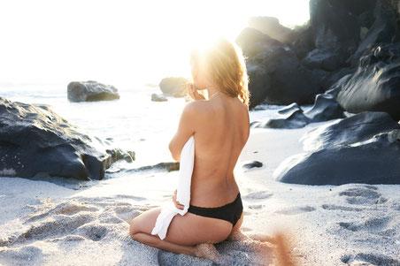 Frau blond kniet am Sandstrand in Bikinihose schwarz
