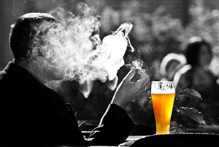 Rauchender Mann  bei einem Glas Bier