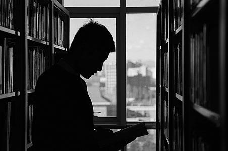 Mann zwischen zwei Bücherregalen