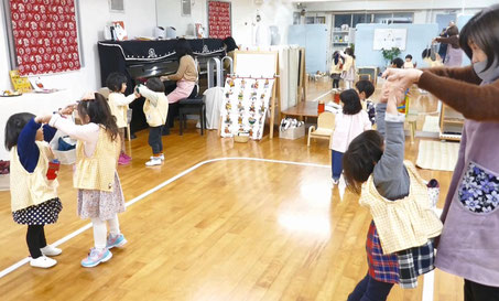2歳児が二人組になって、ピアノに合わせて活動をしています。