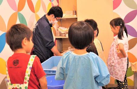 幼稚園児クラスの紙すき体験で、お店の方が説明してくれるのを集中して聞いています。