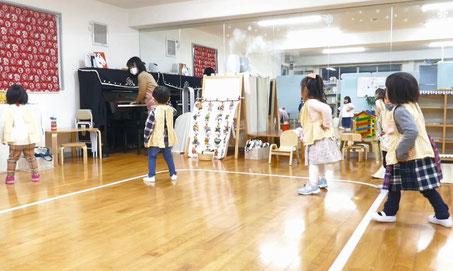 リトミックで2歳児がピアノに合わせて膝の屈伸運動をしています。