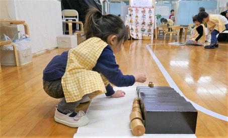 モンテッソーリの個別活動で、2歳児が茶色の階段の活動に円柱を組み合わせて楽しんでいます。