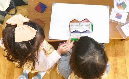 2歳児になるとお友だちといっしょに活動ができるようになります。ふたりでマグネットの立体パズルを楽しんでいます。
