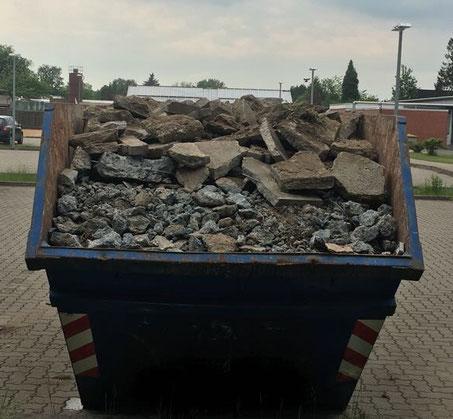 Hamburger Containerdienst bei der Arbeit, beladen mit Steinen.