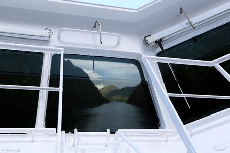 Der Trollfjord spiegelt sich in einer Frontscheibe der Kommandobrücke.