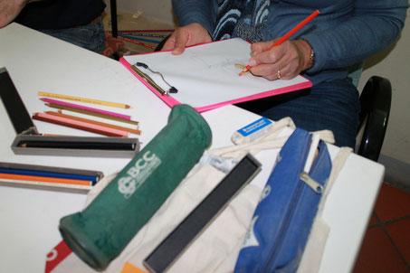 Aixa che disegna due oggetti di ceramica, pastelli su carta.