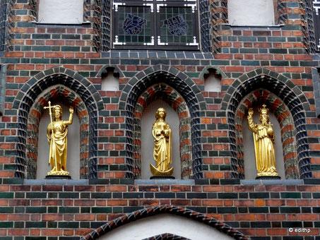 Christus mit dem Kreuzesstab, die Jungfrau Maria auf der Mondsichel und Gottvater als Weltenherrscher mit Krone und Reichsapfel.