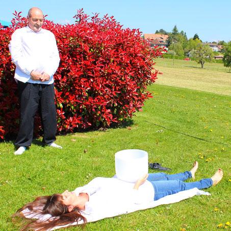 Alain Métraux donne un massage sonore avec un bol de cristal à une femme allongée sur le sol