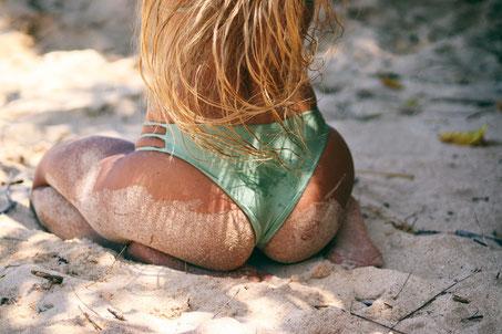 Blonde Frau in Bikini grün kniet am Strand