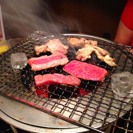 Restaurant mit Tischgrill - Eiswürfel zum Abkühlen der Glut, damit die Flammen nicht das Fleisch verbrennen