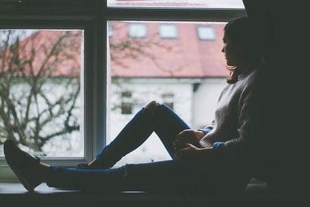 Agoraphobic girl sitting by window.