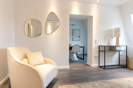 Nettes Wohnzimmer Ambiente mit Coach und Stehlampe.