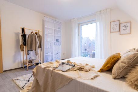 Weiße Couch mit weißen und gelben Kissen und schwarzer Stehlampe.