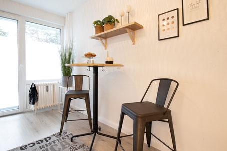 Wohnaccessoires wie Sofa, Lampe und Bilder.