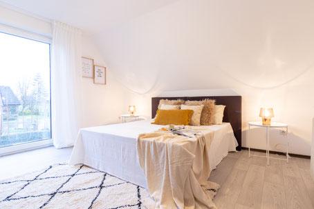 Korbstuhl mit Zimmerpflanze im gestylten Raum.