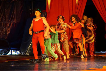 Clowns betreten als Polonaise-Schlange die Manege des Zirkuszeltes
