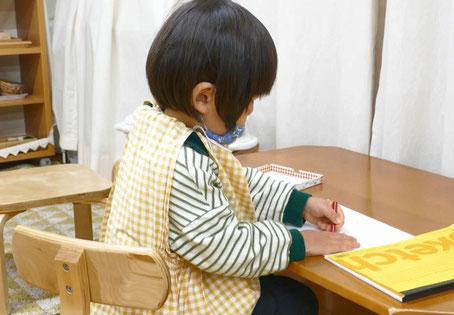 モンテッソーリの活動で、2歳児がクレヨンでアンパンマンを描いています。