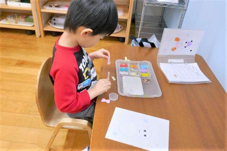 モンテッソーリ教育の個別活動で、2歳児がのりで貼る活動に集中しています。