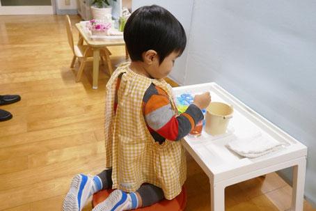 2歳児がモンテソーリの個別活動で色水の活動をしています。