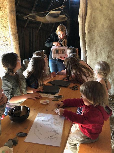 Kinder sitzen an Tisch im rössenzeitlichen Langhaus und bekommen die Bilderwelt der Steinzeit gezeigt