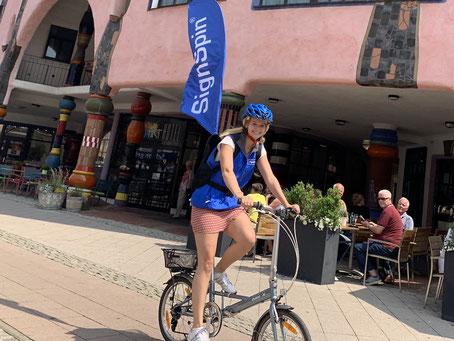 SignSpeederin auf Fahrrad bei einer Kampagne.