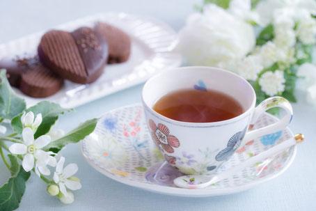ときめくグッズが並んだデスク。ピンクのノートパソコン、ハート形のマカロン、ミルクティーの入ったピンクのカップ&ソーサ、ピンクの目覚まし時計、メモ帳とボールペン、ゴールドピンクのはさみ、スマホ。ピンクのダリアの花。