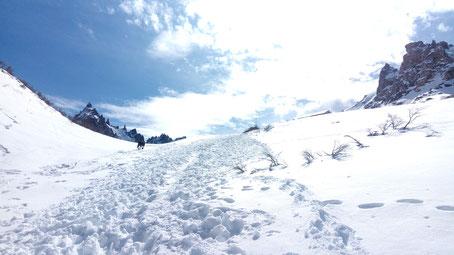 On suit les traces de pas dans cette immensité de neige et on aperçoit les toits du refuge derrière la crête de la colline que nous sommes en train de monter
