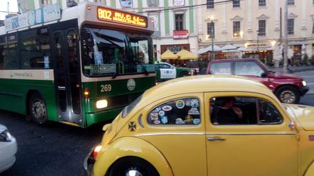 Une coccinelle jaune suivie d'un bus vert et blanc et des terrasses de café en arrière plan, Valparaiso, Chili