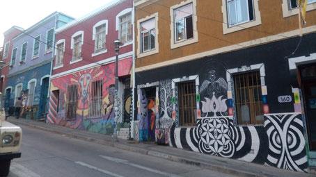 batiments d'habitation à un étage, tous décorés d'un graffiti sur fond coloré