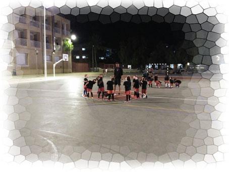 Imagen de 9 niños en medio de una pista de fútbol de un colegio junto a su entrenador. Están estirando.