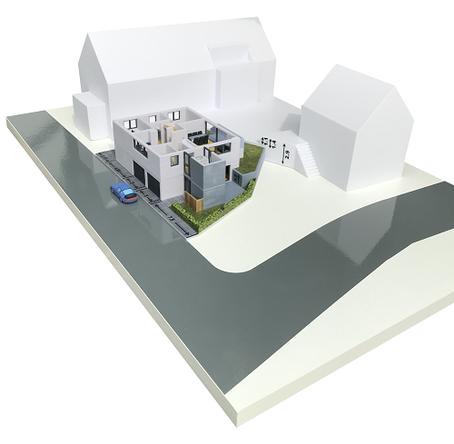 Dieses 3D-Druck Mehrfamilienhaus (farbig) hat abnehmbare Stockwerke, es wurde erstellt, um zu sehen, wie es sich in die Umgebung der Bestandsgebäude (weiß) einfügt.