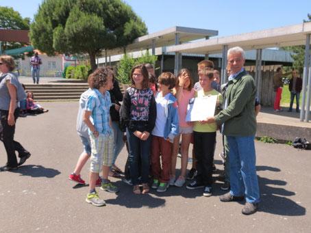 Les élèves du collège Petite Lande remettent le chèque de 10 000 euros au président de l'association Grand-Lieu/Nokoué