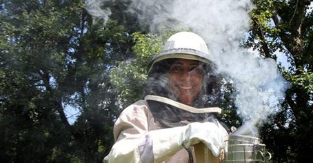 Jenny Castro demonstrates the screened helmet, long-sleeve gloves and other clothing that protect beekeepers, and the smoker used to calm bees while working in the beehive. ANDY JONES/STAFF