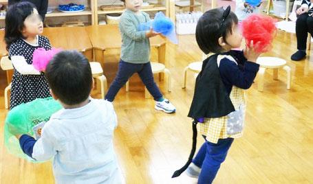 2歳児がリトミックデフカーフを使った活動。丸めたスカーフが手を広げると広がり、まるでお花のようです。