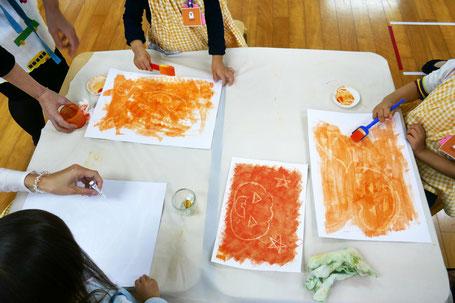 白いくれよんで絵をかき、その上にオレンジの絵の具を塗って、最初の絵を浮かび上がらせます。魔法をイメージして、子どもたちは絵画制作を楽しみました。