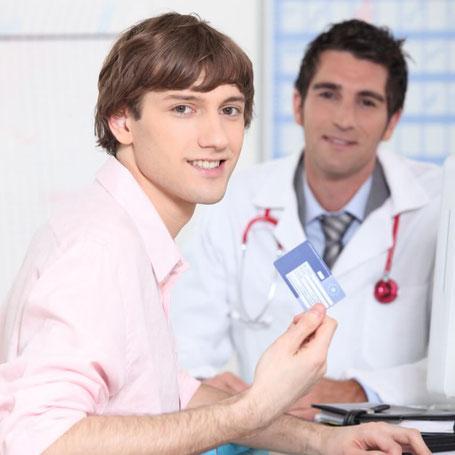 Mann mit Versicherungskarte beim Arzt