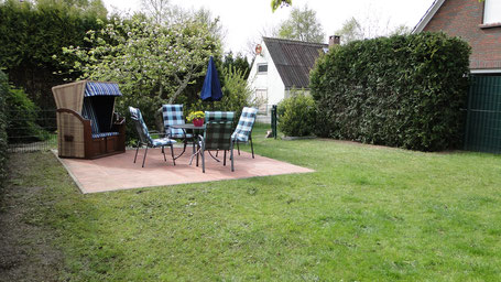 eingezäunter Garten mit Terrasse und Strandkorb