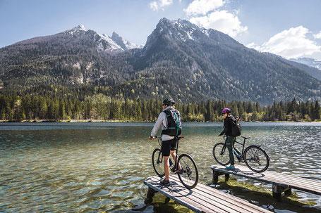 Zwei e-Bike Fahrer am See vor Bergpanorama