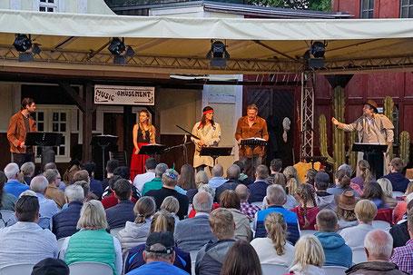 Im Indian Village neben dem Freilichttheater am Kalkberg finden beim Live-Hörspiel 300 Besucher Platz. Sie sitzen im Stile eines Schachbrettmusters in Zweiergruppen zusammen, um die notwendigen Abstände zu wahren. Foto: Karl-May-Spiele/Claus Harlandt