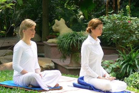 Zwei Frauen sitzen auf einer Matte und meditieren.