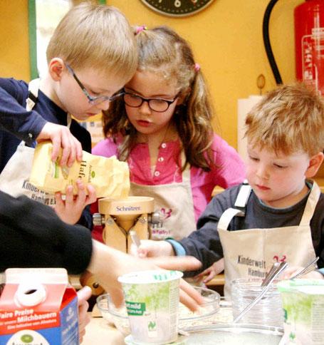 Kita-Kinder bereiten Müsli und quetschen eigene haferflocken.