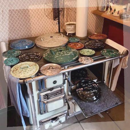 Ein alter Stangenofen in einer Landhausküche auf dem fünfzehn alte Deckel aus Emaille in verschiedenen Größen und Farben zum Trocknen liegen. Die Deckel sind mit Gedichten zum Thema Haus und Garten beschriftet und bemalt.