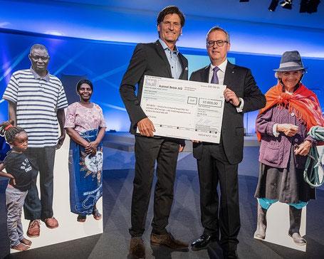 Dr. Manfred Alflen, Aareon Vorstand und Mitglied des Verwaltungsrats der DESWOS, überreicht den Spendenscheck im Rahmen des Galaabends an DESWOS-Generalsekretär Gerhard Müller. Foto: Aareon