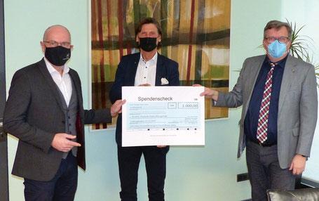 Volker Spindler (Geschäftsführer Kreiswohnungsverband, links) und Clemens Körner (Landrat und Vorstand des KWV, rechts) überreichten dem DESWOS-Generalsekretär Gerhard Müller einen Spendenscheck für die Schaffung von menschenwürdigen Wohnraum im Südsudan.
