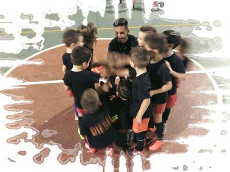 Imagen de nueve niños de 4 y 5 años en una pista de fútbol de un colegio. Todos ellos en círculo junto a su entrenador.