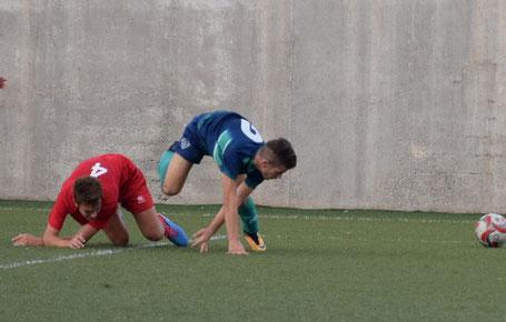 Imagen de un jugador vestido de azul y verde callendo en el césped de un campo de fútbol e intentando levantarse para ir tras el balón. El otro jugador de rojo está tendido en el suelo después de intentar robarle el balón al otro futbolista.